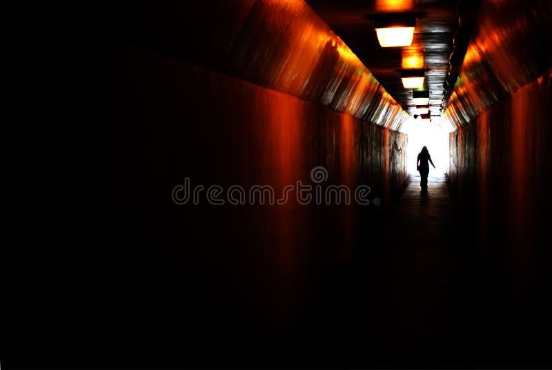 Personne marchant par le tunnel vers la lumière à l'extrémité Accomplissant le but ou laisser des darknenss pour la lumière image stock
