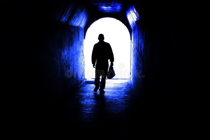 Personne marchant par le tunnel vers la lumière à l'extrémité Accomplissant le but ou laisser des darknenss pour la lumière photos stock