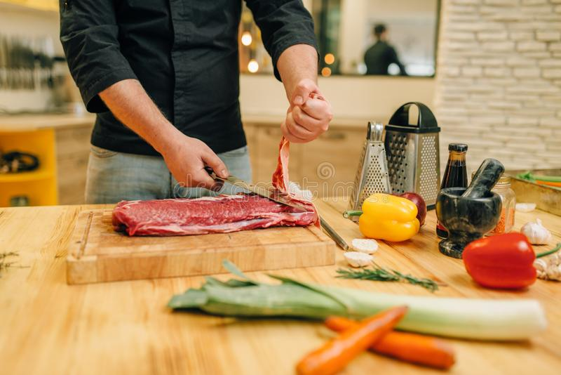 Personne masculine avec de la viande crue de coupes de couteau ? bord photos stock