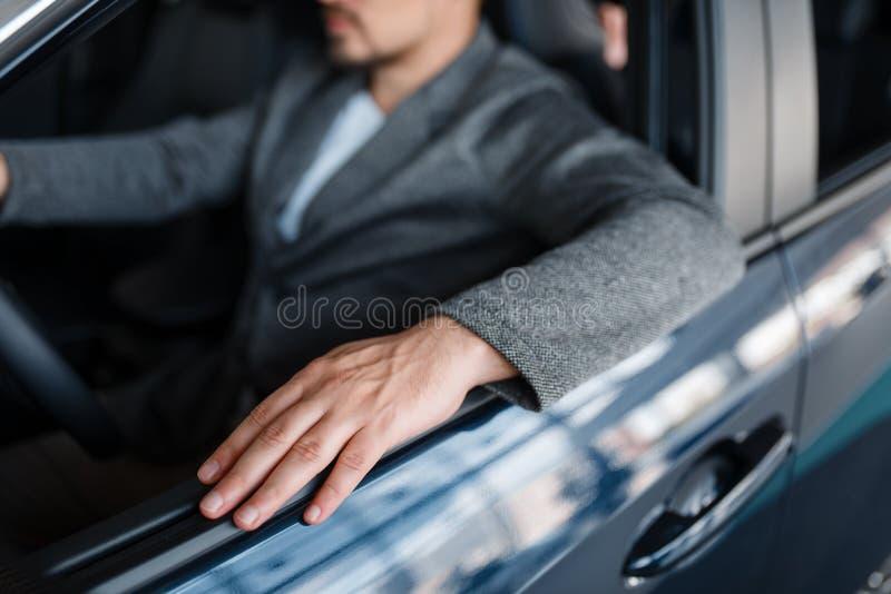 Personne masculine s'asseyant dans la nouvelle voiture, salle d'exposition images stock