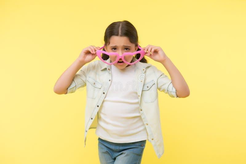 Personne ne m'aime Le visage malheureux de fille d'enfant enlève les lunettes en forme de coeur La fille se sent seule et malheur images stock