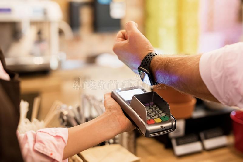 Personne payant au café avec la montre intelligente sans fil sur le terminal de position image libre de droits