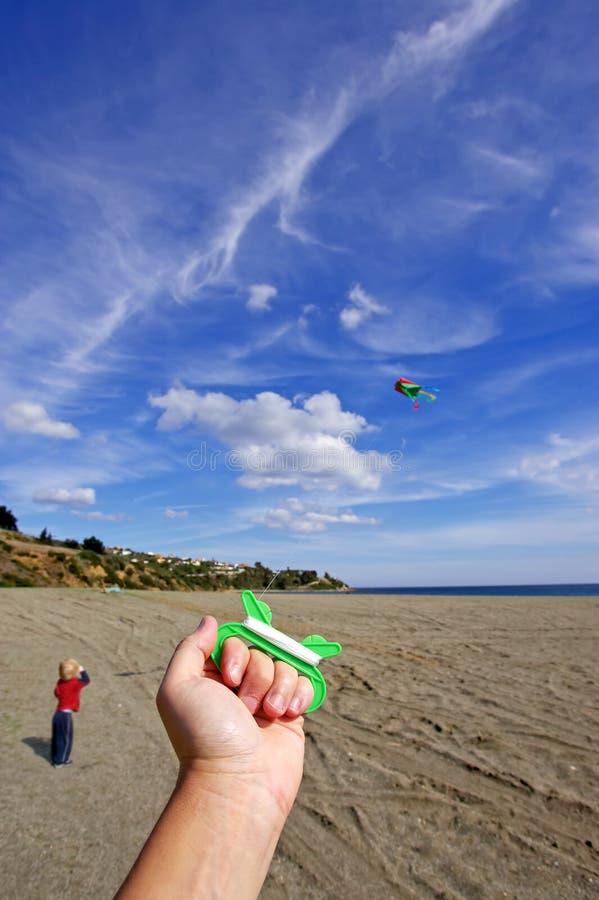 Personne pilotant un cerf-volant un jour ensoleillé avec le garçon observant en fonction photos stock