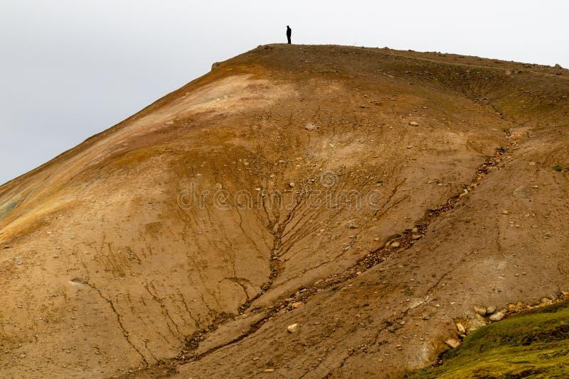 Personne se tenant sur le dessus d'une colline arénacée photos stock