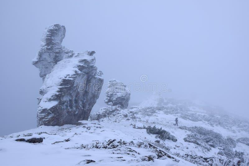 Personne solitaire en montagnes d'hiver à la tempête de neige photos stock