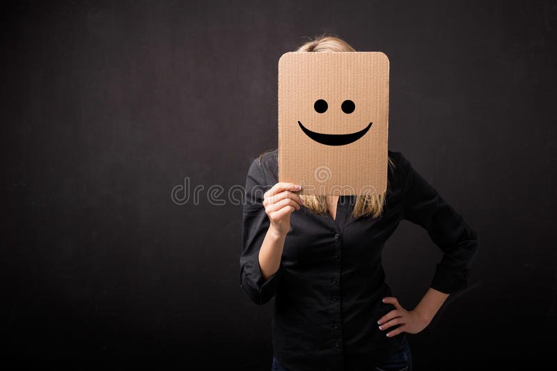 Personne tenant le carton avec le smiley devant son visage photo stock