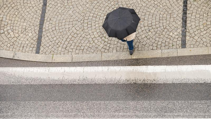 Personne tenant le parapluie sur la rue photo libre de droits