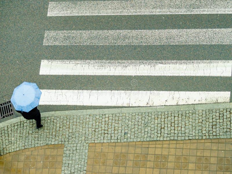 Personne tenant le parapluie sur la rue image stock