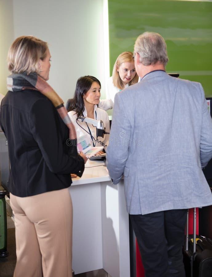 Personnel aidant les passagers supérieurs au bureau d'enregistrement d'aéroport images libres de droits