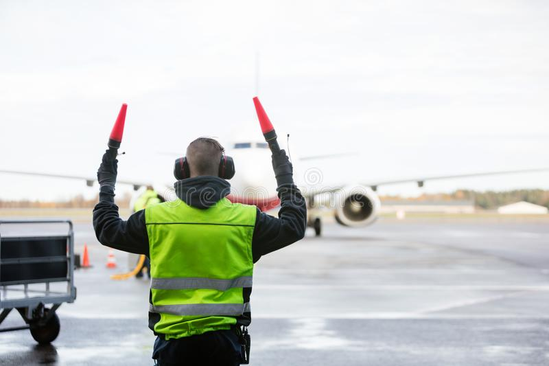 Personnel de piste signalant à l'avion image libre de droits
