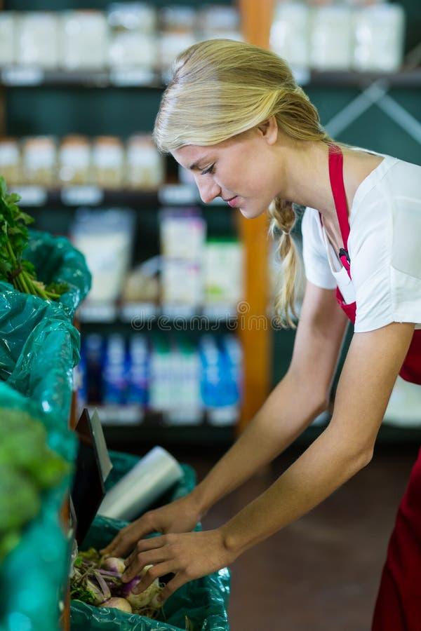 Personnel féminin vérifiant des légumes dans la section organique photographie stock libre de droits