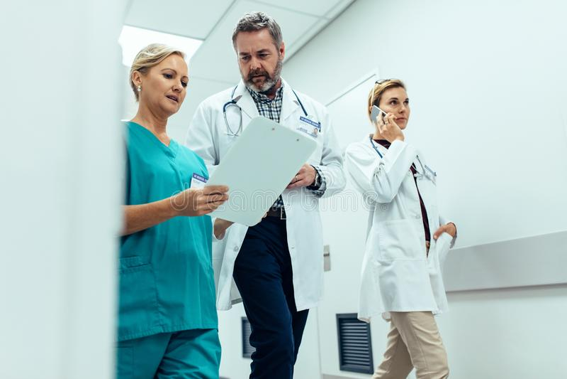 Personnel hospitalier occupé discutant dans le couloir d'hôpital images stock