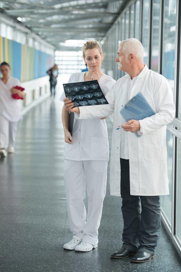 Personnel médical regardant le rayon X dans le couloir d'hôpital images stock