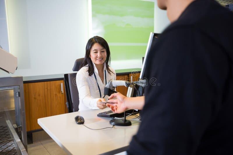 Personnel prenant le passeport du passager masculin à l'enregistrement d'aéroport photos stock