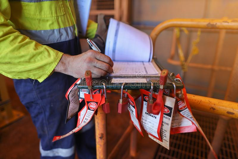 Personnel red locks attached with danger tag together with safety isolation permit lock box stock image
