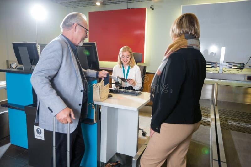 Personnel vérifiant des passeports des passagers à l'aéroport images stock