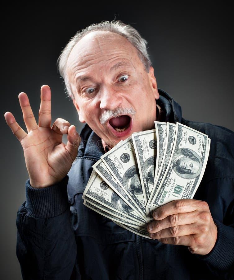 Personnes âgées heureuses avec le ventilateur de l'argent image stock