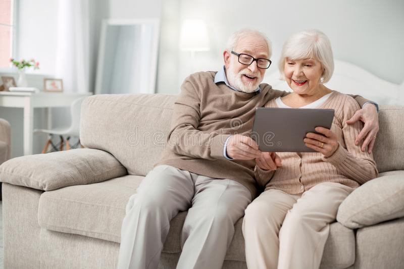 Personnes âgées joyeuses regardant l'écran de comprimé photo libre de droits