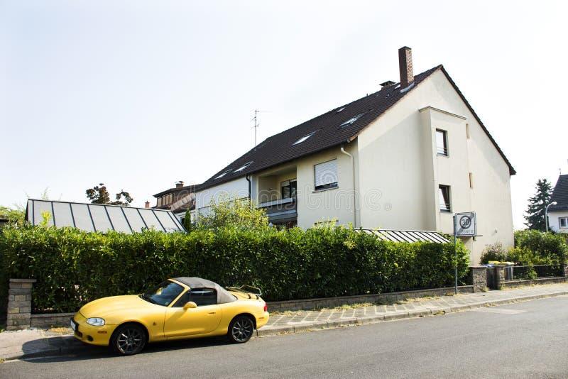 Personnes allemandes arrêtant la voiture de sport jaune à près de la route sur la route d'Ilvesheimer images stock