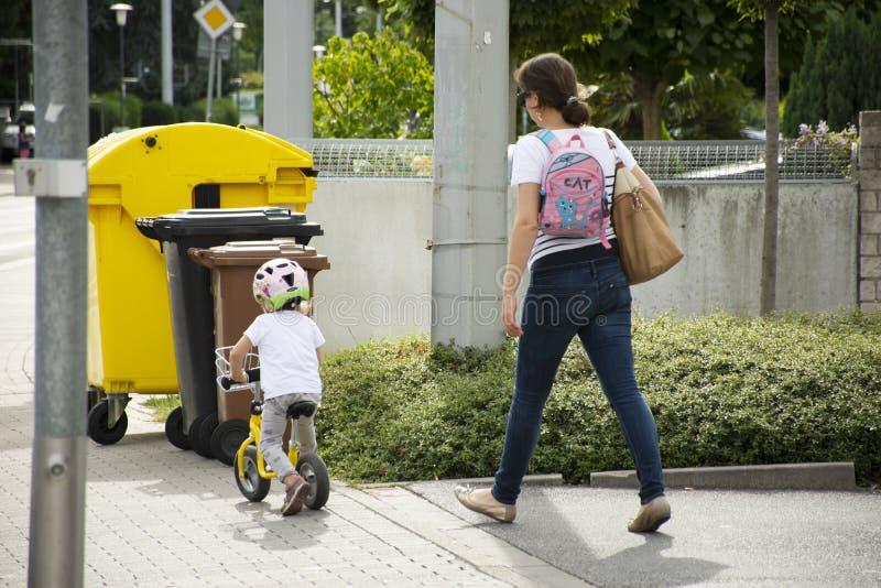 Personnes allemandes de mère regardant la pratique en matière de fille d'enfants faisant un cycle sur le sentier piéton près de l photo stock