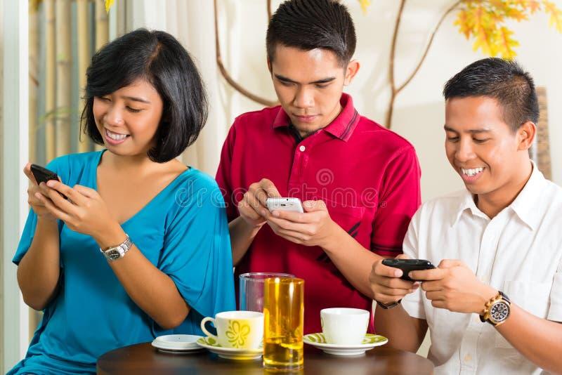 Personnes asiatiques ayant l'amusement avec le téléphone portable images stock