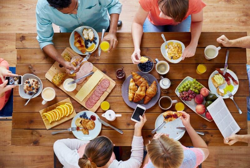 Personnes avec des smartphones mangeant de la nourriture à la table images libres de droits