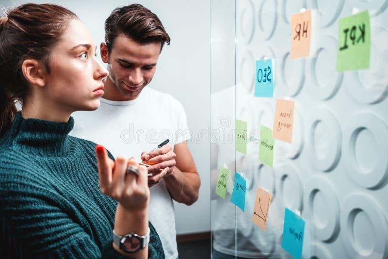 Personnes coworking intelligentes préparant la stratégie commerciale et signalées sur un mur en verre collant de note photographie stock