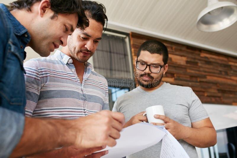 Personnes créatives passant par des documents lors d'une réunion informelle photo libre de droits