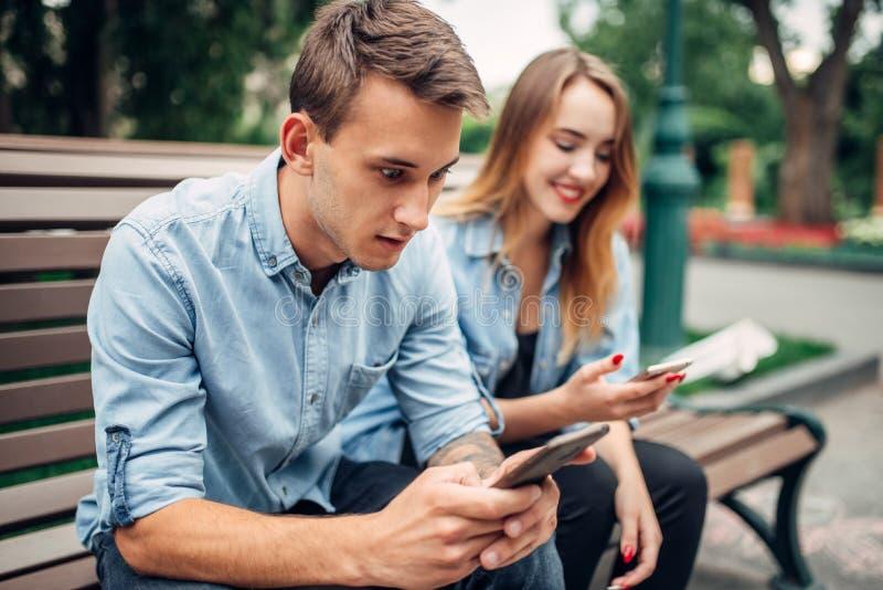 Personnes dépendantes de téléphone, couples utilisant des smartphones image stock