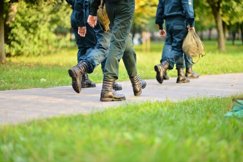 Personnes dans l'uniforme militaire marchant sur la route image libre de droits