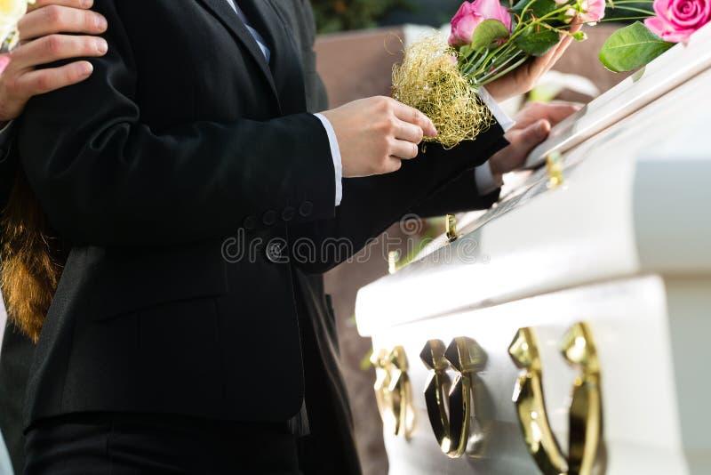 Personnes de deuil à l'enterrement avec le cercueil photo libre de droits