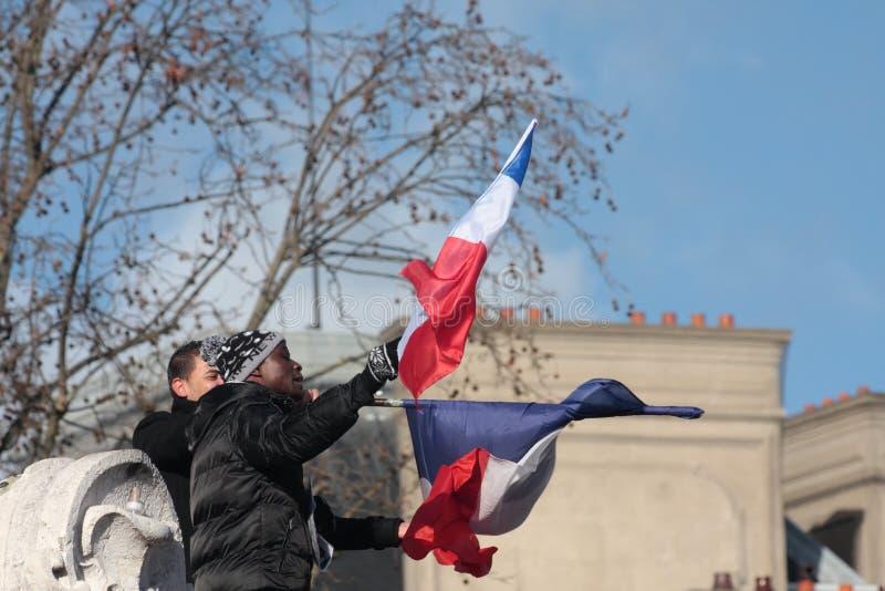 Personnes de race noire ondulant le drapeau français, Paris image stock