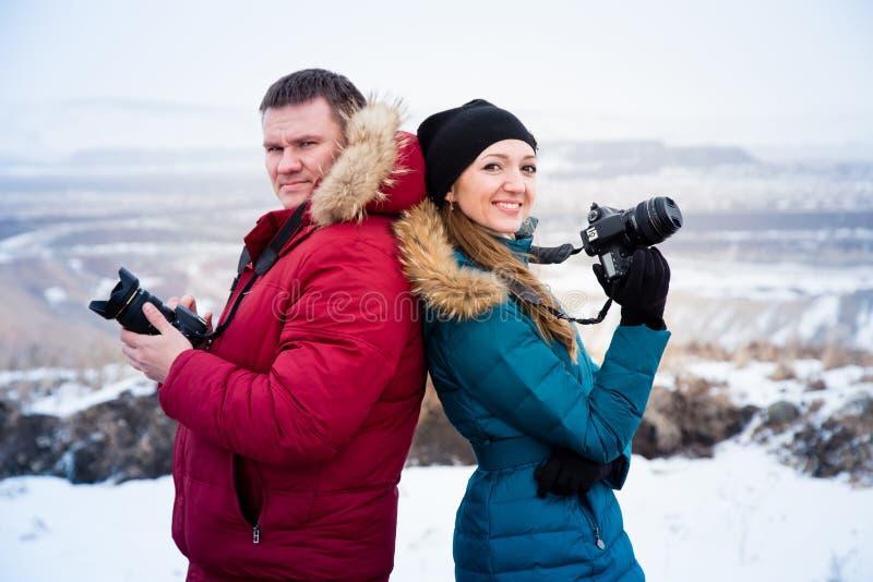 Personnes de sourire avec des appareils-photo dans les mains des montagnes images stock
