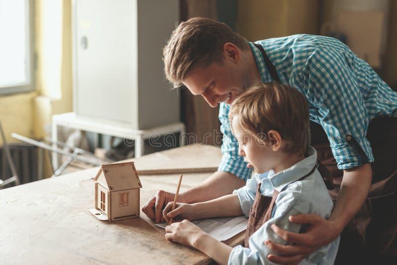 Personnes de sourire avec une maison en bois photos stock