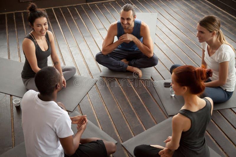 Personnes de sourire diverses s'asseyant sur des tapis parlant avant train de yoga photos libres de droits