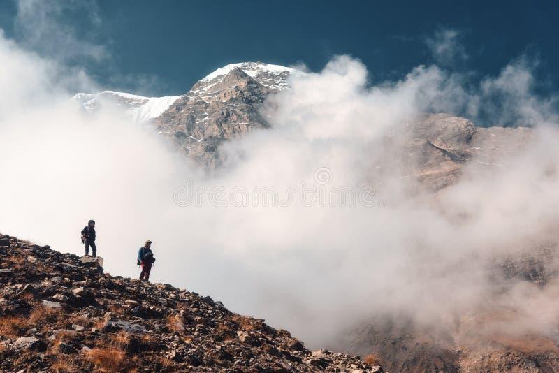 Personnes debout sur la traînée de montagne en bas nuages photo stock