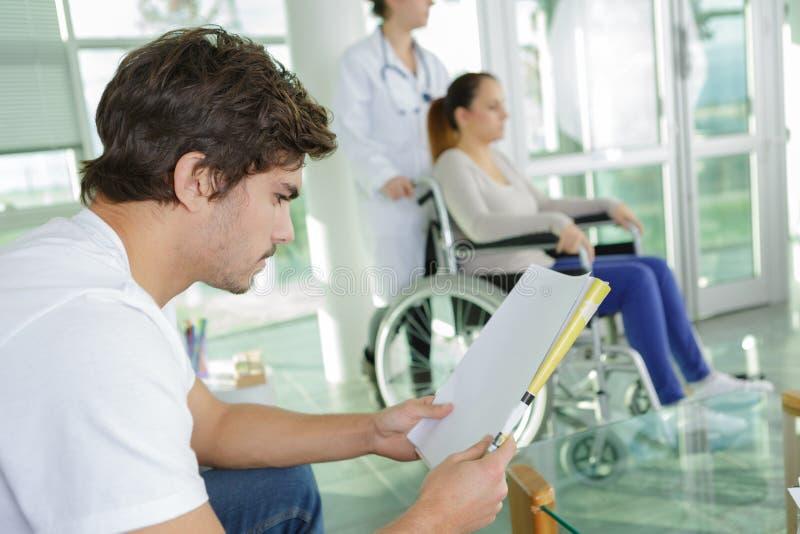Personnes différentes s'asseyant dans l'hôpital de salle d'attente photos stock