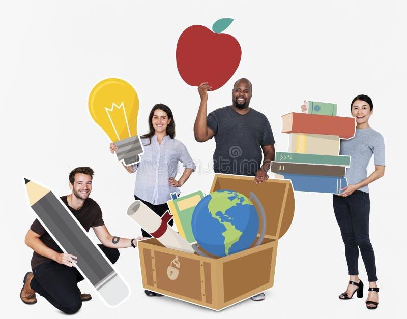 Personnes diverses heureuses tenant les icônes éducatives image libre de droits