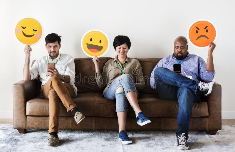 Personnes diverses reposant et tenant des logos d'emojis images stock
