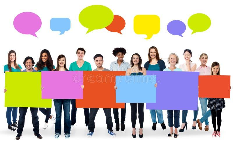 Personnes diverses tenant les conseils colorés photo stock