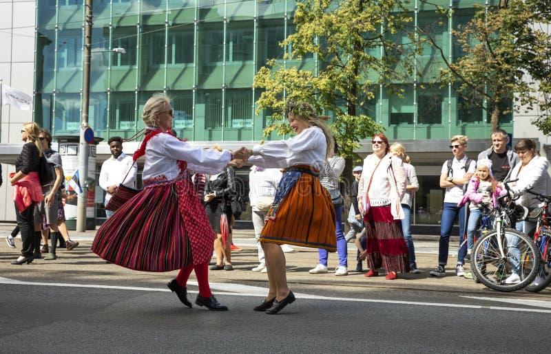 Personnes estoniennes dans l'habillement traditionnel marchant les rues de Tallinn photographie stock libre de droits