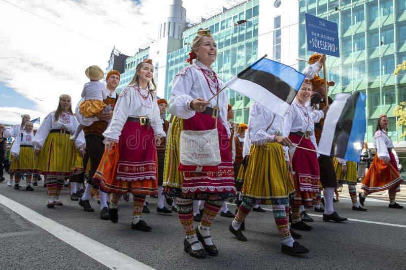 Personnes estoniennes dans l'habillement traditionnel marchant les rues de Tallinn images libres de droits