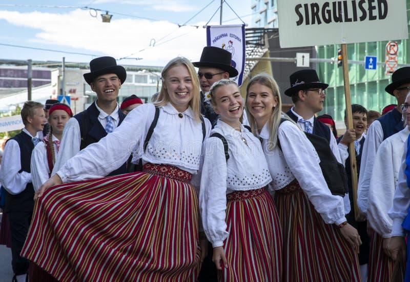 Personnes estoniennes dans l'habillement traditionnel marchant les rues de Tallinn photographie stock