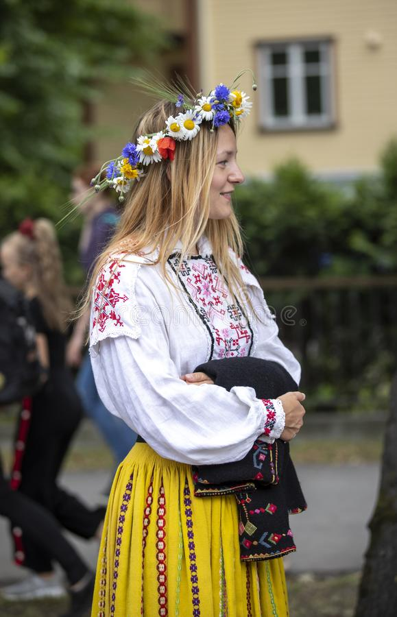 Personnes estoniennes dans l'habillement traditionnel marchant les rues de Tallinn photos stock