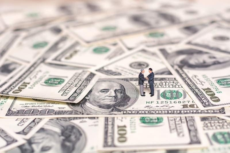 Personnes et argent miniatures Concept créatif d'une affaire Les hommes d'affaires se serrent la main image libre de droits