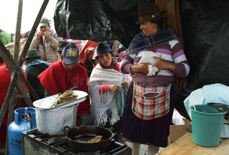 Personnes ethniques équatoriennes avec les vêtements indigènes prenant le petit déjeuner sur un marché rural de samedi de village images stock
