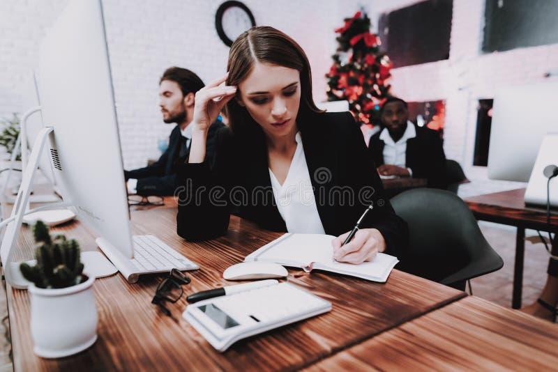 Personnes fatiguées travaillant dans le bureau la soirée du Nouveau an photographie stock