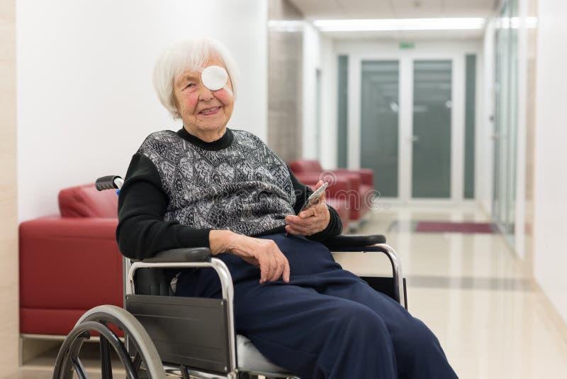 Personnes ?g?es seules 95 ann?es de femme s'asseyant au fauteuil roulant utilisant le t?l?phone portable moderne photos libres de droits