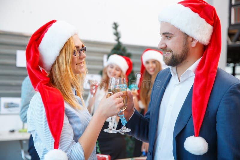 Personnes gaies de bureau dans des chapeaux de Santa à la fête de Noël sur le fond de bureau Concept d'an neuf image stock