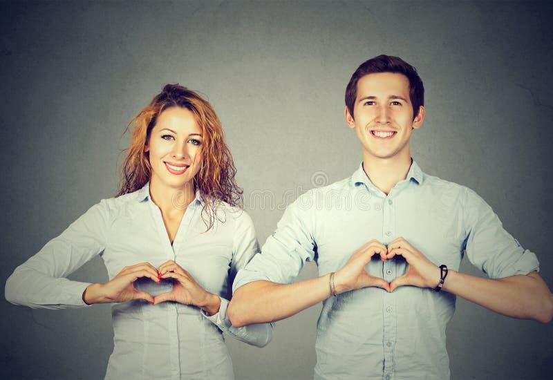 Personnes gaies montrant des coeurs avec des mains photographie stock libre de droits
